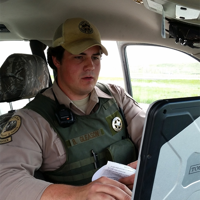 FWP Game warden working at a computer in his vehicle