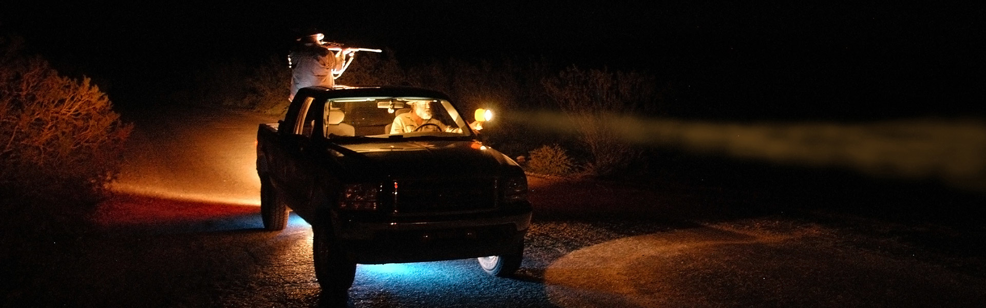 FWP wardens in a truck using lights to look out into a field at night.