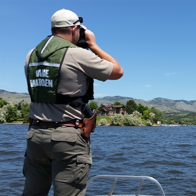 An FWP Warden using binoculars on the water